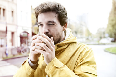 Portrait of young man holding coffee cup - FEXF000054