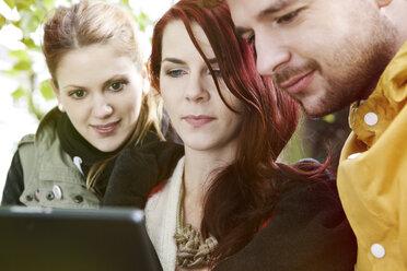 Three friends using digital tablet - FEXF000056