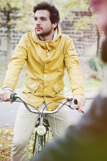Germany, North Rhine-Westphalia, Cologne, young man sitting on bicycle - FEXF000068