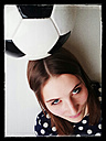 Young woman with a football on her head - JATF000596