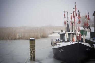Germany, Mecklenburg-Western Pomerania, Ruegen, Gager, Fishing boat in frozen water - MJ000669
