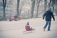 Father pulling sledge with son in snow - MJ000712