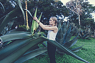 Italy, Sicily, young woman freeing a giantic  Agave americana in the Botanical Garden of Palermo - MFF000755