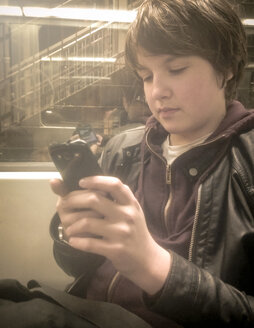 Teenage Boy in the Subway reading on his smartphone, Berlin, Germany - MVC000067