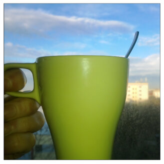 Good Morning, a green Cup of Coffee, held in hand against blue sky with clouds - MVC000063