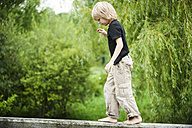 Little boy balancing on railing of wooden boardwalk - PAF000276