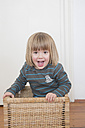 Portrait of smiling little girl standing in a basket - LVF000495