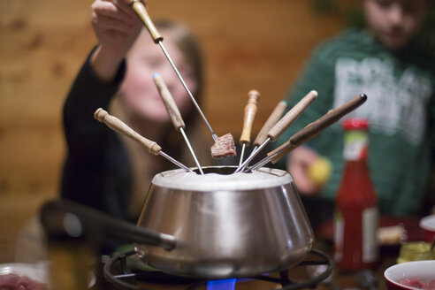 Hot pot with fondue forks, two children in the background - SAR000226