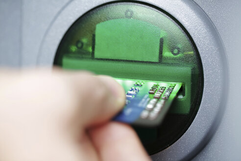 Man pushing credit card at cash dispenser, close-up - JATF000598