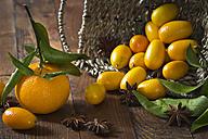 Tangerine (Citrus reticulata), kumquats and star anise (Illicium verum) on wooden table - YFF000004