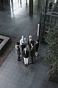 Group of businesspeople with laptop talking in lobby - CHA000021