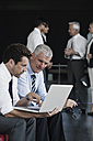 Two businessmen with laptop in office lobby - CHAF000034