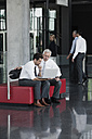 Two businessmen with laptop in office lobby - CHAF000019