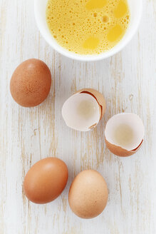 Bowl of breaked open eggs and egg shells on wooden table - EVGF000336