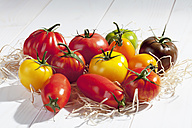 Different tomatoes on wood wool and wooden table - CSF020739