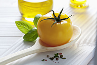 Yellow tomato on wooden spoon, olive oil, basil and peppercorns on wooden table - CSF020718