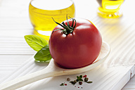 Red tomato on wooden spoon, olive oil, basil and peppercorns on wooden table - CSF020681