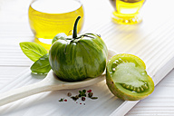 Green tomato on wooden spoon, olive oil, basil and peppercorns on wooden table - CSF020675