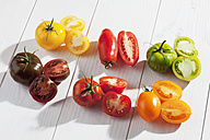 Different sliced tomatoes on wooden table - CSF020672