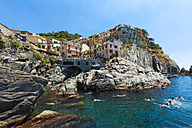 Italy, Liguria, La Spezia, Cinque Terre, Manarola, view to village, bathing people in front - AMF001767