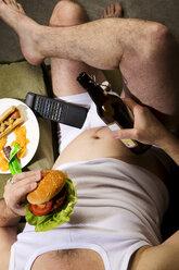 A man eats junk food - MAEF007681
