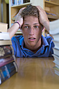 Germany, Baden-Wuertemberg, stressed young student with stack of books in a library - CHAF000107