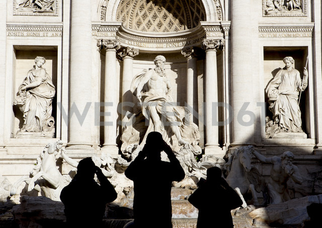 Italy, Rome, view to Trevi Fountain with silhouettes of three tourist in front - DIS000452