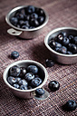 Three zinc bowls of blueberries on cloth - SBDF000508