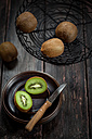 Wire basket and plate of whole and sliced kiwi fruits on wooden table - SBDF000492