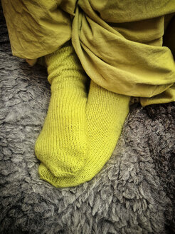 Feet of a girl with hand-knitted socks and baggy pants on sheepskin, Laupheim, Baden-Wuerttemberg, Germany, Europe - HAF000255