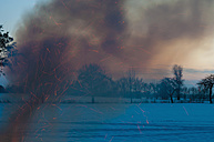 Germany, Saxony, smoke and sparkling of camp fire at winter landscape - MJF000803