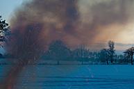 Germany, Saxony, smoke and sparkling of camp fire at winter landscape - MJF000803