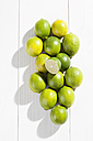 Limes and leaves on wooden table - CSF020742