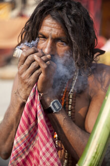 India, Uttar Pradesh, Varanasi, portrait of Sadhu smoking chillum pipe - JBA000054