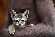 India, Uttar Pradesh, Varanasi, kitten in the arm of a Sadhu - JBA000059