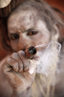 India, Uttar Pradesh, Varanasi, portrait of Sadhu smoking chillum pipe - JBA000065