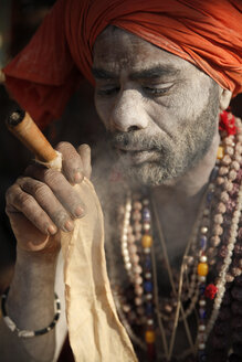 India, Uttar Pradesh, Varanasi, portrait of Sadhu smoking chillum pipe - JBA000068