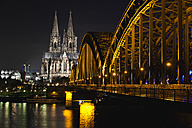 Germany, North Rhine-Westphalia, Cologne, Cologne Cathedral and Hohenhollern Bridge over the Rhine river by night - ZMF000194