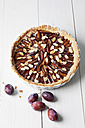 Tart pan with plum cake and plums on white wooden table - CSF020810