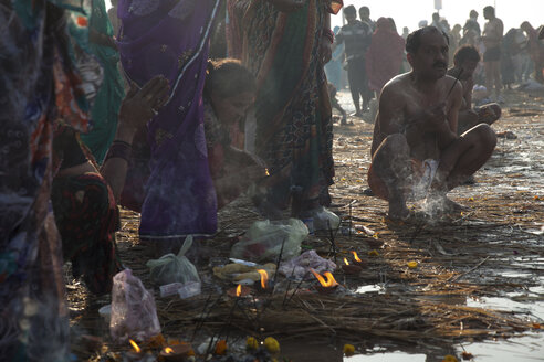 India, Uttar Pradesh, Allahabad, Kumbh Mela pilgrimage, People with joss sicks at riverside - JBA000077