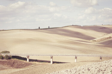Italy, Tuscany, Val d'Orcia, Rolling landscape with bridge - MJF000850