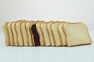 Single slice of black bread in a row of toast bread - AKF000318