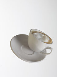 White coffee cup with white coffee and saucer flying in front of white background - AKF000322