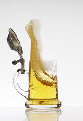 Beer splashing out of beer mug in front of white background - AKF000303