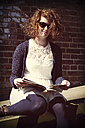 Young woman with sunglasses holding magazine - HOHF000417