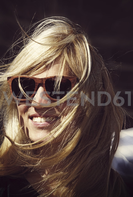 Smiling young woman with blowing hairs wearing sunglasses - HOHF000412