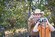 USA, Texas, Man and kid with binoculars - ABAF001205