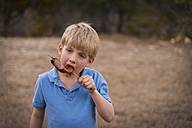 USA, Texas, Boy eating barbecue sausage - ABAF001198