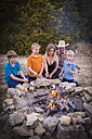 USA, Texas, Family Roasting marshmallows over camp fire - ABAF001196