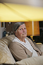 Senior woman sitting on a couch at living room - JATF000661